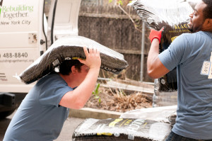 """Now that's using your head!"" A volunteer loading mulch into a wheelbarrow."